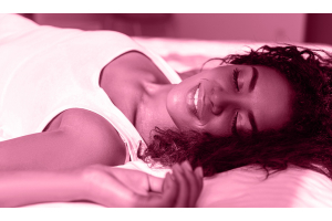 a woman lies on the bed looking satisfied and happy