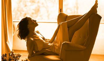 woman lounges in an armchair breathing deeply