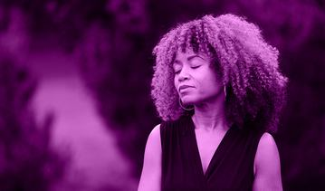 A Black woman with a hopeful expression and closed eyes breathes deeply in an outdoor setting.