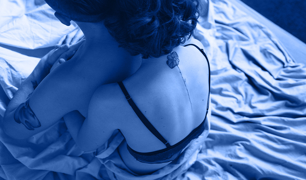 one person embraces another in a bed with rumpled sheets