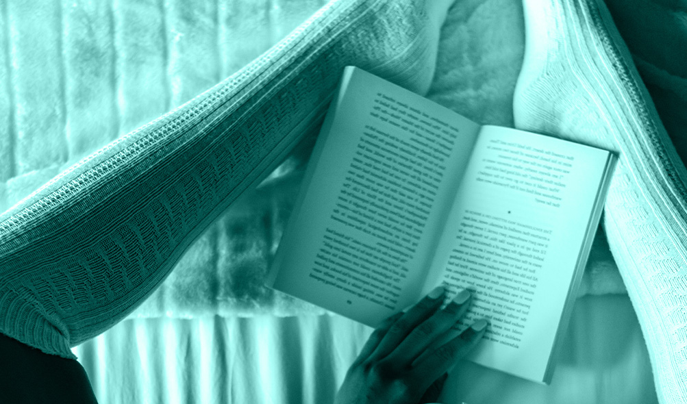 a book is held open between two legs wearing tall stockings on a bed