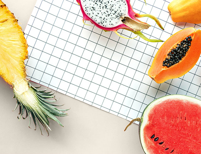 halved tropical fruits on a grid background - pineapple, papaya and watermelon